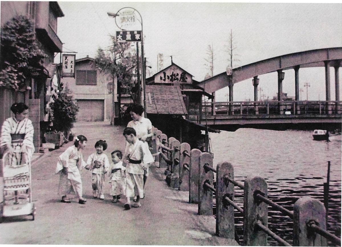 昭和42年頃、まだ護岸がなかった頃の柳橋で、妹たちの手をひく治さん(画像提供:小松屋)